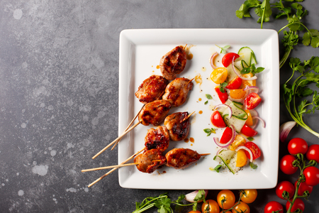 Delicious grilled meat skewers with summer salad of cherry tomatoes, cucumbers and red onions.