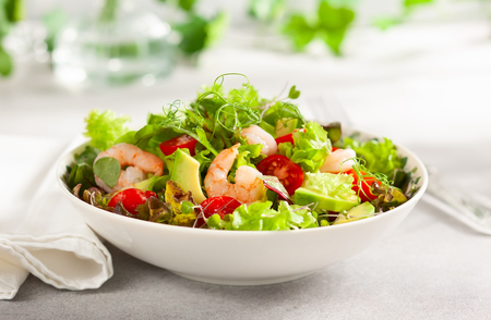 Fresh summer salad with shrimp, avocado and tomato cherry in bowl on light table.