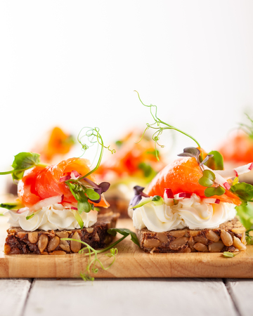 Mini canapes with smoked salmon, soft cheese and fresh veggies on gluten-free seed bread for party.