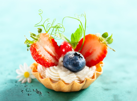 Summer berry tartlets  with cream and fresh berries on blue