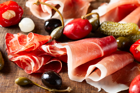 Assort of sliced jamon, salami, ham with olives, capers, pickles and stuffed red peppers on wooden Stock Photo - 124054559