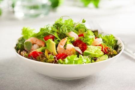 Frisse zomersalade met garnalen, avocado en tomatenkers in kom op lichttafel.