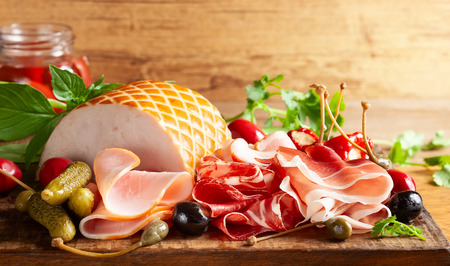 Assort of sliced jamon, salami, ham with olives, capers, pickles and stuffed red peppers on wooden Stock Photo - 124054552