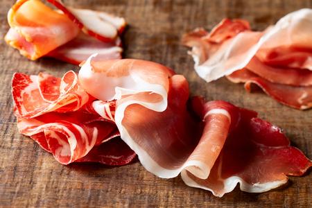 Assort of sliced jamon, salami, ham  on wooden Stock Photo