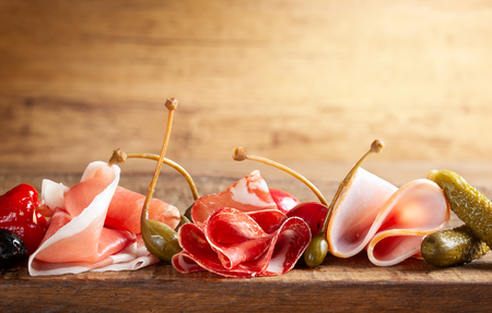 Assort of sliced jamon, salami, ham with olives, capers, pickles and stuffed red peppers on wooden Stock Photo - 124054737