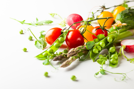 Fresh green  peas pods with sprouts, radish, tomatoes and green asparagus on white wooden Stock Photo