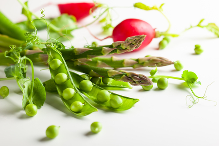Fresh green  peas pods  with  sprouts, radish and green asparagus on white wooden