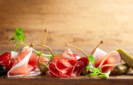 Assort of sliced jamon, salami, ham with olives, capers, pickles and stuffed red peppers on wooden Stock Photo - 124054926