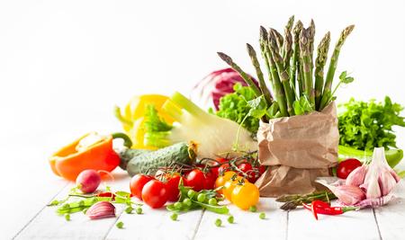 Diverse soorten verse groenten en kruiden op een witte houten