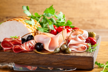 Assort of sliced jamon, salami, ham with olives, capers, pickles and stuffed red peppers on wooden