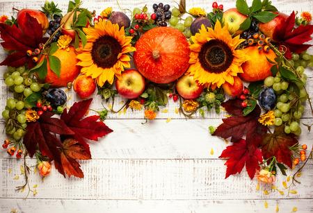 Erntedankfesthintergrund mit Herbstkürbissen, Früchten und Herbstblättern auf Holztisch. Draufsicht, Herbstkonzept mit Kopierraum.