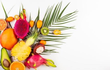 Still life with fresh assorted exotic fruits on a palm leaf. Concept of healthy eating with fruits. Top view. Stock Photo