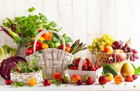 Stilleven met verschillende soorten verse groenten, fruit en bessen in manden op een witte houten tafel. Concept van gezond eten.