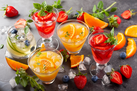 Assortment summer non-alcoholic cocktails with fresh berries, herbs and fruits on dark background. Stock Photo