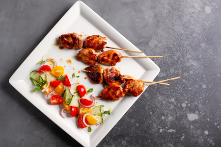 Delicious grilled meat skewers with summer salad of cherry tomatoes, cucumbers and red onions.Top view with copy space. Banco de Imagens