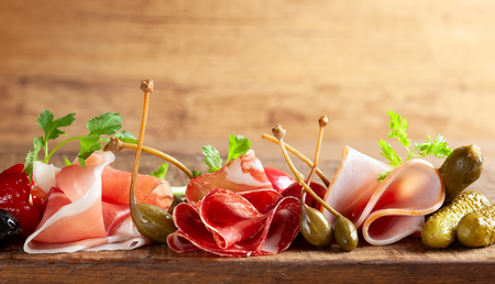 Assorti of sliced jamon, salami, ham with olives ,capers, pickles and stuffed red peppers on wooden background.