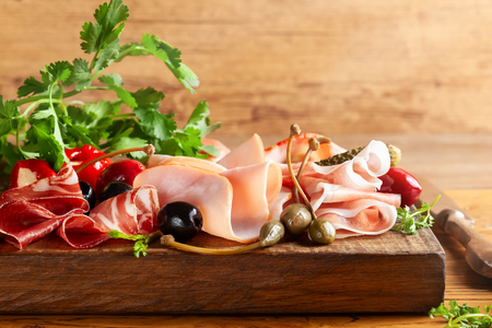 Assorti of sliced jamon, salami, ham with olives ,capers, pickles and stuffed red peppers on wooden background. Various meat appetizers on wooden board.