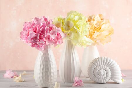 Bouquets of beautiful hydrangea in vases on the  table. Still life with colorful flowers hortensia.
