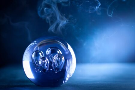 Crystal ball in dark blue smokey background with copy space. Crystal ball fortune-teller with magical lighting. Imagens - 126492072