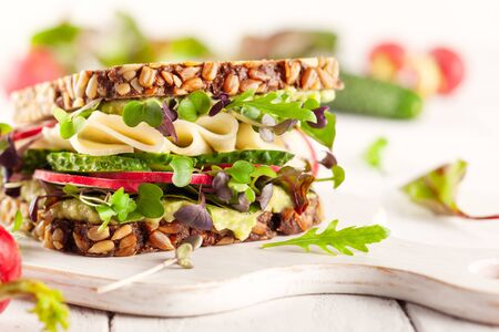 Fresh vegetarian  sandwich  with creamy avocado, cheese and fresh veggies the wooden board. Concept healthy eating. Vegetarian sandwich. Imagens - 126492073