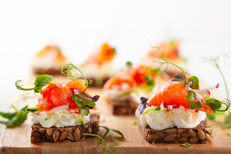 Mini canapes with smoked salmon, soft cheese and fresh veggies on gluten-free seed bread for party. Imagens - 126492074