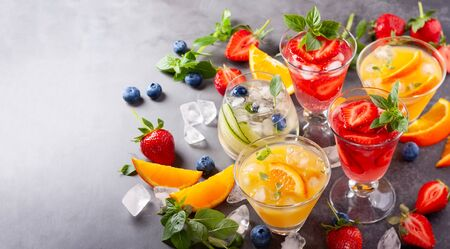 Assortment summer non-alcoholic cocktails with fresh berries, herbs and fruits on dark background.