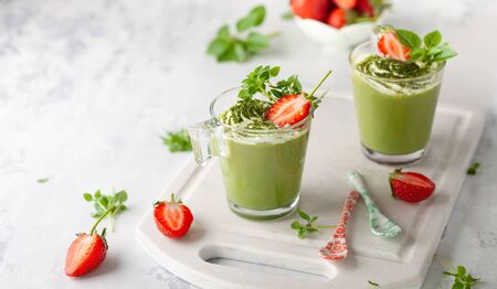 Matcha green tea panna cotta  with coconut milk topped with strawberry  in  glasses. Concept healthy gluten-free dessert for summer. Imagens - 126492079