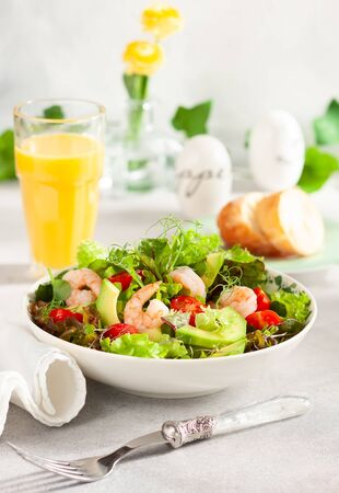 Fresh summer salad with shrimp, avocado and tomato cherry in bowl on light table. Concept of healthy eating. Imagens - 126492080