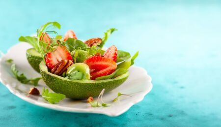 Stuffed avocado  with strawberries  and nut . Healthy summer appetizer. Imagens