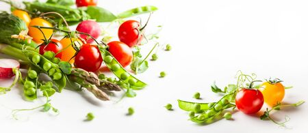 Fresh green  peas pods with sprouts, radish, tomatoes and green asparagus on white wooden background. Concept of healthy eating, fresh vegetables.