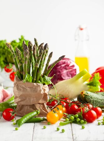 Various types of fresh vegetables and herbs on a  white wooden background. Concept of healthy eating, fresh vegetables.