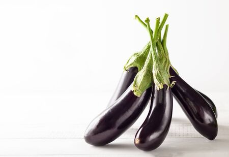 Fresh eggplants on a white wooden table. Concept of healthy eating, fresh vegetables.