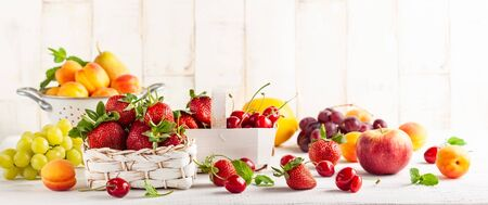Still life with various types of fresh fruits and berries in baskets on a white wooden table. Concept of healthy eating.