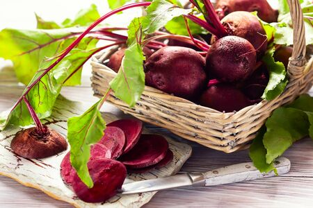 Fresh organic beetroot with green leaves in a basket on a  wnite wooden table. Imagens - 126492106
