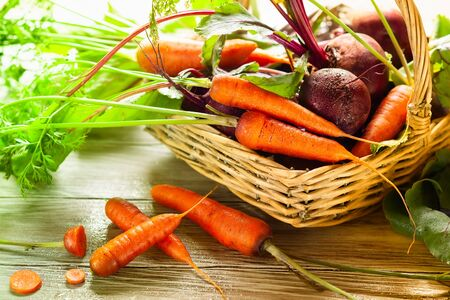 Fresh organic beetroot and carrot with green leaves in a basket on a  wnite wooden table. 写真素材