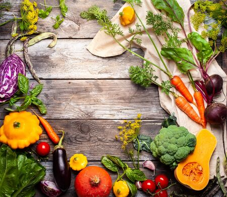 Assortment of raw vegetables on a vintage wooden background.Organic  healthy nutrition concept. Top view with copy space. Imagens - 126492108