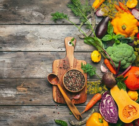 Assortment of raw vegetables and vintage wooden kitchen utensils on wooden background.Organic  healthy nutrition concept. Top view with copy space. Imagens - 126492111
