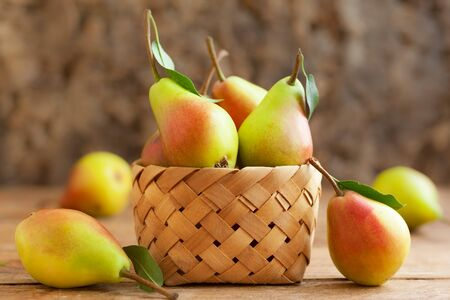 Fresh ripe pears in basket on the wooden table. Organic fruits, concept of healthy eating with copy space. Imagens - 126492127