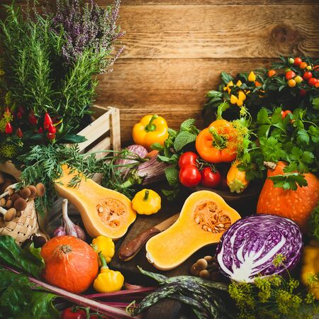 Assorted seasonal vegetables and fresh herbs on a rustic wooden table. Imagens - 126492129