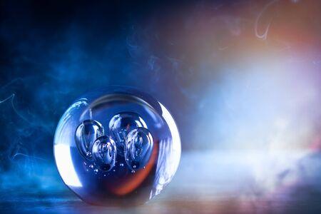Boule de cristal sur fond smokey bleu foncé avec espace de copie. Diseuse de bonne aventure boule de cristal avec éclairage magique. Banque d'images