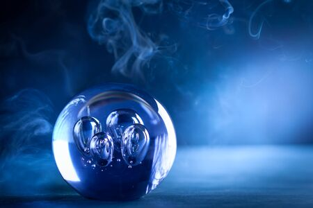 Crystal ball in dark blue smokey background with copy space. Crystal ball fortune-teller with magical lighting.