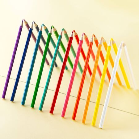 Colour pencils set on light yellow background. Pencils are reflected in the mirror surface. Imagens - 126952113