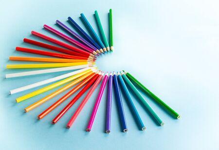 Colour pencils set on light blue background with copy-space.