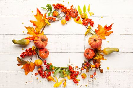Autumn concept with pumpkins, flowers, autumn leaves and  rowan berries on a white rustic background. Festive autumn decor, flat lay with copy space. Imagens