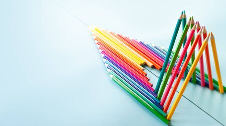 Colour pencils set on light blue background with copy-space. Back to school concept. Pencils are reflected in the mirror surface.