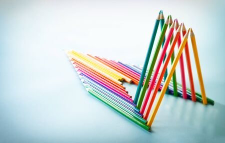 Colour pencils set on light blue background with copy-space. Back to school concept. Pencils in form of rocket are reflected in the mirror surface. Imagens