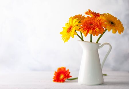 Beautiful bouquet of red and yellow flowers in white vase on wooden table, front view. Autumn still life with flowers.