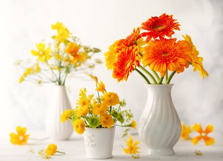 Beautiful bouquets of red and yellow flowers in white vases on wooden table, front view. Autumn still life with flowers.