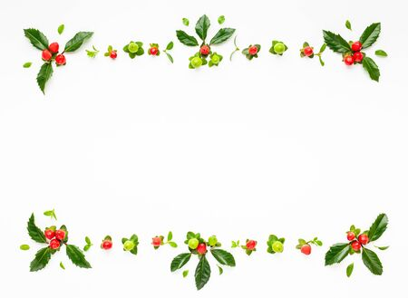 Christmas composition  with branches of spruce and holly with red berries on white background. Merry christmas greeting card with empty space for holiday text. Flat lay.