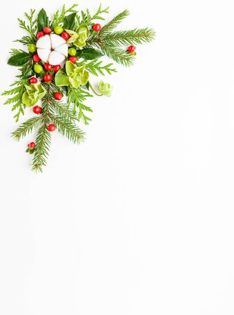 Christmas composition  with branches of spruce and holly with red berries on white background. Merry christmas greeting card with empty space for holiday text.